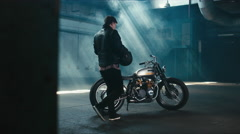 Caucasian male biker mounts custom cafe racer motorcycle in large warehouse Stock Footage