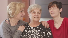 Women generation portrait: daughter and grandchildren kiss grand mother Stock Footage