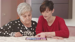 Young grandaughter shows to her grandmother tablet's functions Stock Footage