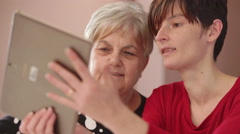 Grandmother and her daughter take a selfie with tablet Stock Footage
