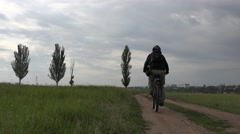 Cyclist rides along path among green meadows. Background tree and city Stock Footage