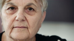 elderly woman serene and tranquil looks to the camera Stock Footage