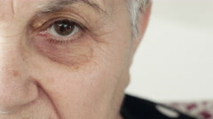 Focus on old woman eye looks to the camera Stock Footage