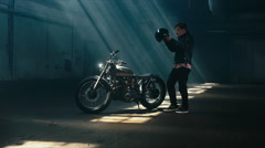 Young male biker in mounts his custom cafe racer motorcycle in warehouse garage Stock Footage