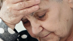 tired, worried old woman with her hand on forehead - stock footage