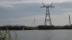 Pontoon bridge across the river on a background of the electric towers, reeds - stock footage