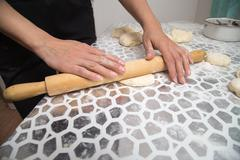 Sheeting the dough with a rolling pin in the kitchen Stock Photos