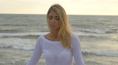 Meditation in yoga: charming woman while meditating with closed eyes by the sea - stock footage