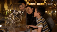 4K Asian family in natural history museum looking at a skeleton inside glass jar - stock footage