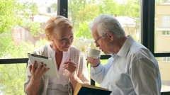 Happy lovely retired couple standing opposite each other with tablet and book Stock Footage