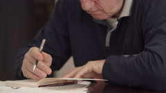 Elder man at his desk while reading and underlining with a pencil a book Stock Footage