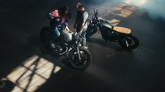 Wide overhead shot of male biker teaching his girlfriend to ride a motorcycle - stock footage