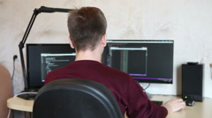 Student programmer writes a program while sitting at the computer. Back view Stock Footage