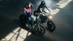 Wide overhead shot of male biker having a chat with a girl on a motorcycle Stock Footage