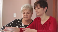 Grand-daughter shows to her grandmother how works tablet Stock Footage