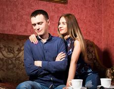 problems in family relationships, a young couple sitting on the couch. man hurt - stock photo
