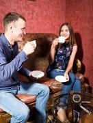 family relationships, a young couple sitting on a sofa and drink tea, they are - stock photo