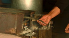 Hand of old woman puts a wood in metal stove at hut in a mountain village Stock Footage