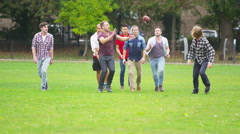 4K Energetic young male friends playing rugby or American football in the park - stock footage