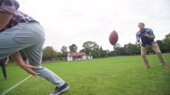 4K Energetic young male friends playing rugby or American football in the park Stock Footage