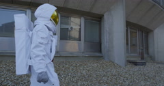4K Astronaut looking for signs of life outside abandoned power station - stock footage