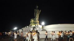 People walk with candles around a large Buddha statue Stock Footage