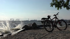 Bike standing on riverbank with large waves, storm sontrast at sunset - stock footage