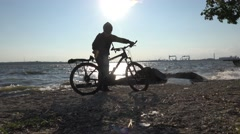 Cyclist is bike on sand on riverbank with large waves, storm sontrast sunset Stock Footage