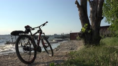 Bike standing on riverbank with large waves, storm sontrast at sunset Stock Footage