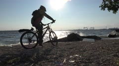 Cyclist rides through sand on riverbank with large waves, storm sontrast sunset Stock Footage