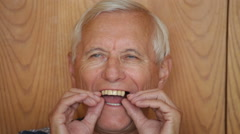 Senior man showing denture and teeth Stock Footage