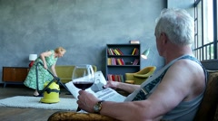 happy elderly woman dancing with vacuum cleaner, husband reading newspaper and - stock footage