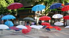 Art installation of suspended colored umbrellas  above walking pedestrian street Stock Footage