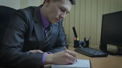 Businessman working in office. He draws attention to the portrait of his beloved Stock Footage
