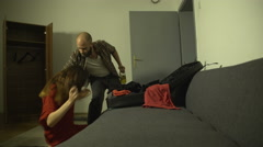 Beaten woman packing suitcase, drunken man coming, throws woman and her clothes. Stock Footage