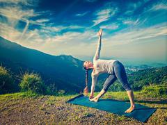 Woman doing Ashtanga Vinyasa yoga asana Utthita trikonasana - stock photo