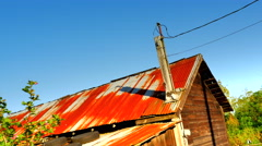 4K Rusty Tin Corrugated Metal Roof on Old Wooden Shanty Building - stock footage