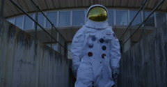 4K Astronaut on an exploration trip, walking away from mission control building. - stock footage