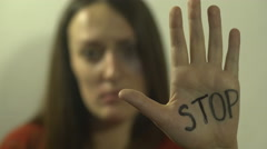 Beaten girl with bruise on eye, raising hand with written message STOP, close up Stock Footage
