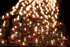 church candles whit weaving flames on black background - stock photo