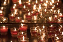 Church candles whit weaving flames on black background Stock Photos