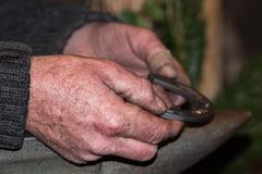 Old retired man hand detail while working iron Stock Photos