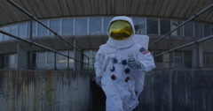 4K Funny astronaut doing a dance as he walks away from mission control building. - stock footage