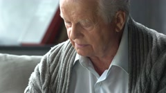 Elderly caucasian man reading a book in a modern apartment Stock Footage