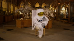 4K Funny astronaut returned to earth sitting down for a break in museum Stock Footage