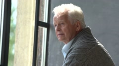 Elderly caucasian man look at window, lost in thought Stock Footage