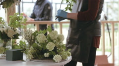 Woman florist decorates a bouquet of flowers - stock footage
