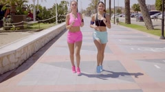 Two attractive athletic young women jogging Stock Footage