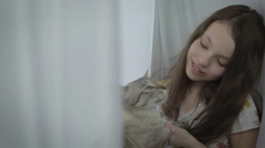 Beautiful little girl gently communicates with your loved cat at window Stock Footage