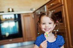 Little girl in the kitchen smiling, eating lollipop Stock Photos